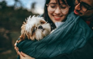 couple hugs their dog